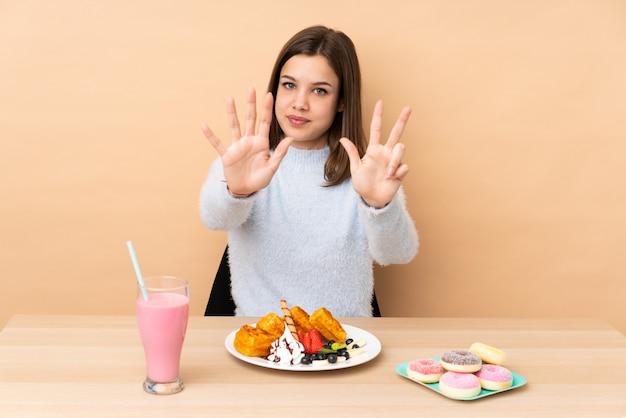 Menina adolescente comendo waffles na parede bege contando oito com os dedos