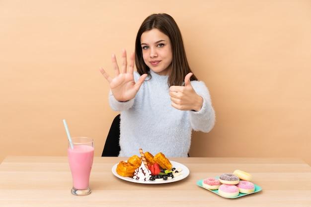 Menina adolescente comendo waffles na parede bege contando seis com os dedos