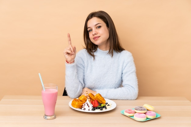 Menina adolescente comendo waffles na parede bege mostrando e levantando um dedo em sinal dos melhores