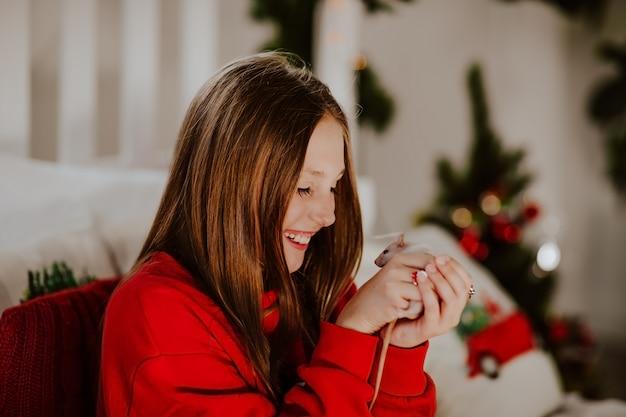Menina adolescente consideravelmente nova na camiseta vermelha que mantém o ratinho contra o natal.