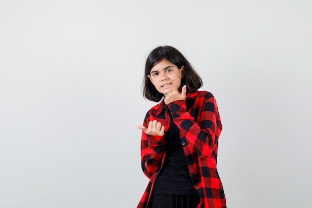 Menina adolescente convidando para entrar em uma camisa casual e parecendo feliz. vista frontal.