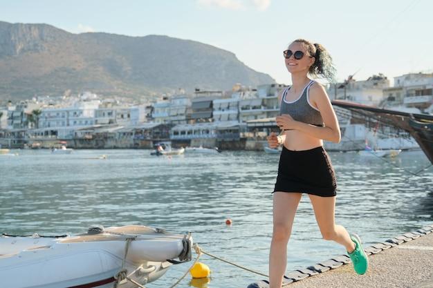 Menina adolescente correndo correndo no passeio marítimo