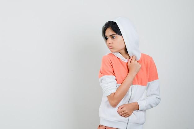 Menina adolescente dando um passo para o lado na jaqueta branca e parecendo assustada.