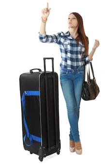 Menina adolescente de 16 anos, com uma grande bolsa de viagem preta com rodas.