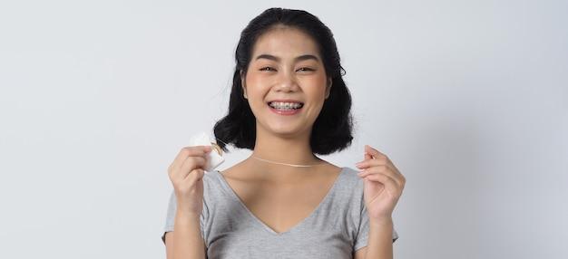 Menina adolescente de aparelho dentário sorrindo olhando para uma câmera dentes brancos com aparelho azul.