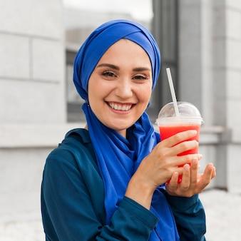 Menina adolescente de azul posando com um smoothie