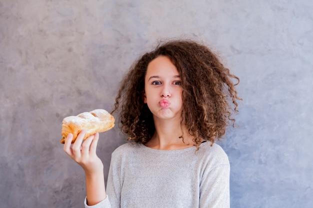 Menina adolescente de cabelo encaracolado comendo croissant