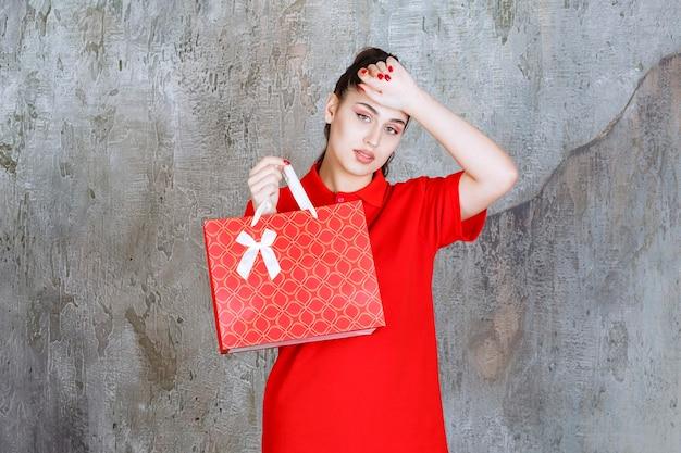 Menina adolescente de camisa vermelha, segurando uma sacola de compras vermelha e parece cansada e com sono.