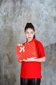 Menina adolescente de camisa vermelha, segurando uma sacola de compras vermelha e parece confusa e pensativa.