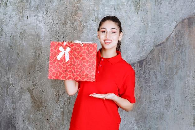 Menina adolescente de camisa vermelha segurando uma sacola de compras vermelha