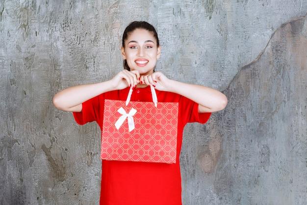 Menina adolescente de camisa vermelha, segurando uma sacola de compras vermelha.