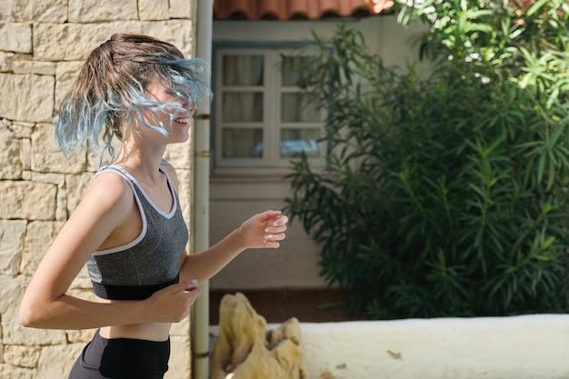 Menina adolescente de esportes de corrida ao ar livre, dia ensolarado de verão, estilo de vida ativo e saudável dos jovens, cópia espaço