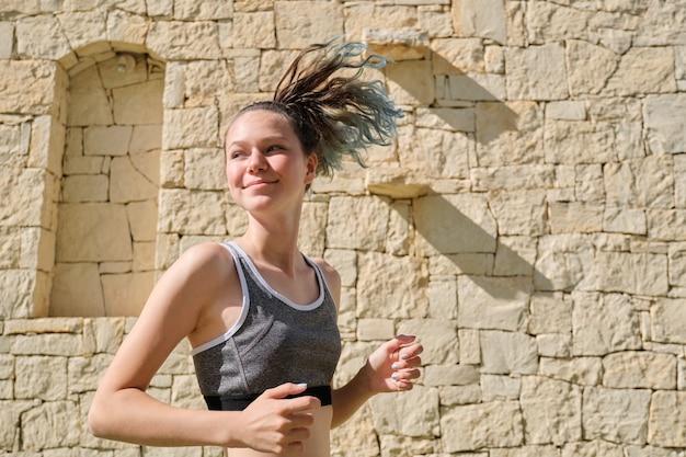 Menina adolescente de esportes de corrida ao ar livre, dia ensolarado de verão, estilo de vida ativo e saudável dos jovens, espaço de cópia