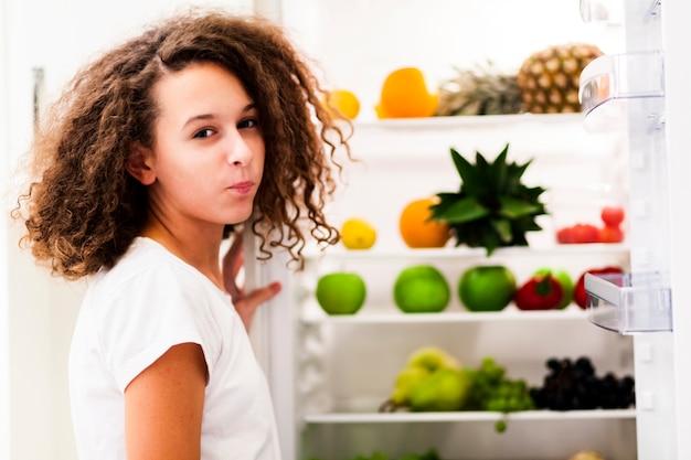 Menina adolescente de idade perto de geladeira