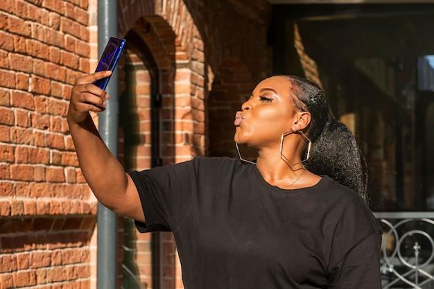Menina adolescente de lado tirando uma selfie