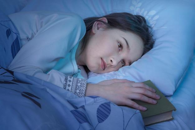 Menina adolescente de pijama, deitada na cama, tarde da noite, tentando dormir.