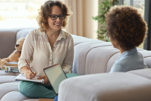 Menina adolescente de raça mista e sua professora usando laptop para estudar online enquanto dá uma aula no