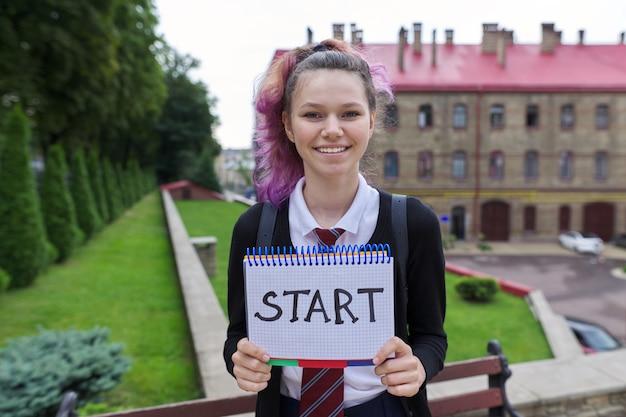 Menina adolescente de uniforme segurando o bloco de notas com início de palavra. de volta à escola, de volta à faculdade, início do ano letivo. colegial olhando para a câmera, plano de fundo do prédio da escola
