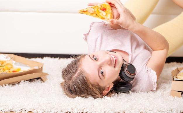 Menina adolescente deitado com pizza no chão