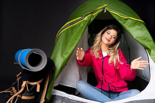 Menina adolescente dentro de uma barraca de acampamento verde isolada em um fundo preto apresentando e convidando para vir com a mão