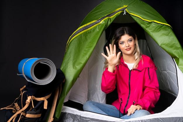 Menina adolescente dentro de uma barraca de acampamento verde na parede preta, contando cinco com os dedos