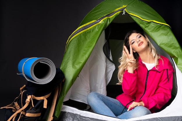 Menina adolescente dentro de uma barraca de acampamento verde na parede preta feliz e contando três com os dedos