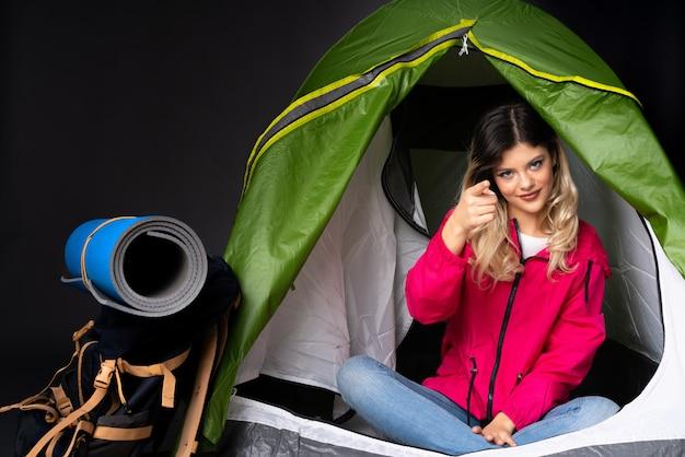 Menina adolescente dentro de uma barraca de acampamento verde na parede preta, mostrando e levantando um dedo