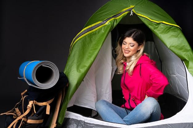 Menina adolescente dentro de uma barraca de acampamento verde