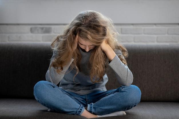 Menina adolescente deprimida com emoções e sentimentos tristes, sentada no sofá em casa