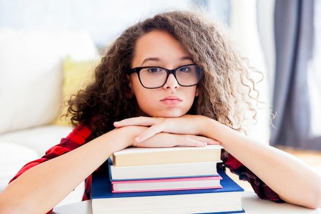 Menina adolescente descansando em livros no quarto