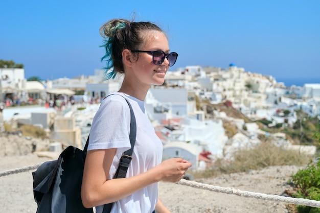 Menina adolescente descansando na ilha grega de santorini, mulher olhando para longe, arquitetura de fundo branco da vila de oia, mar, céu nas nuvens, espaço de cópia