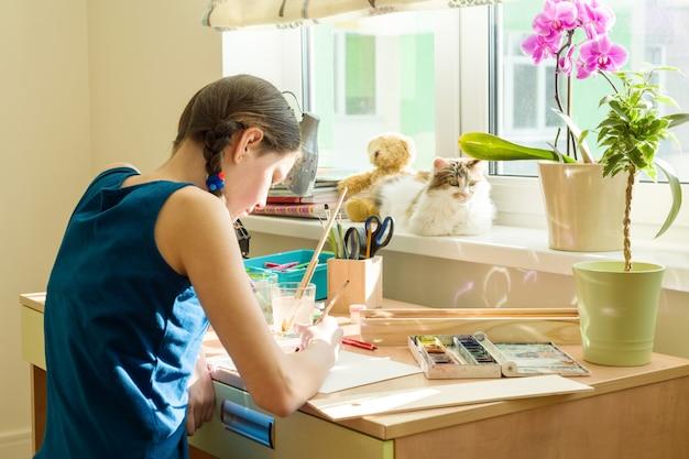 Menina adolescente desenha aquarela, sentado em casa à mesa