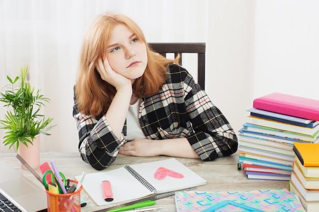 Menina adolescente desenha coração no caderno, conceito de primeiro amor