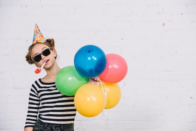 Menina adolescente, desgastar, óculos de sol, segurando, partido, chifre, em, dela, boca, e, pegando, balões coloridos, em, mão