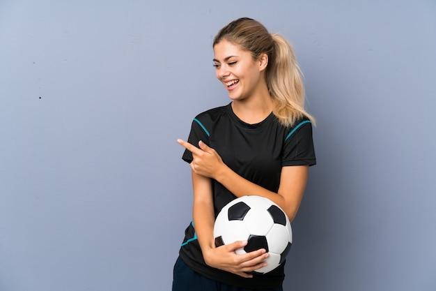 Menina adolescente do jogador de futebol loira sobre a parede cinza, apontando para o lado para apresentar um produto