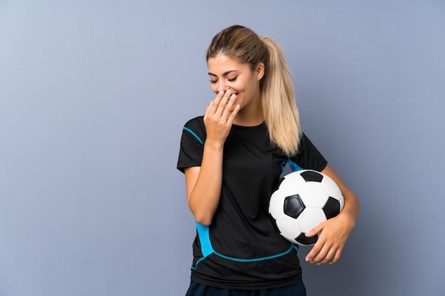 Menina adolescente do jogador de futebol louro sobre a parede cinzenta que sorri muito