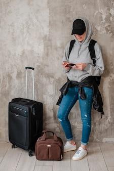 Menina adolescente do moderno com as malas de viagem no fundo de um muro de cimento na sala de espera do transporte.