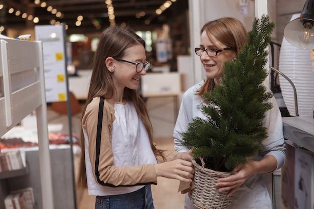 Menina adolescente e mãe comprando árvore de natal em loja de móveis