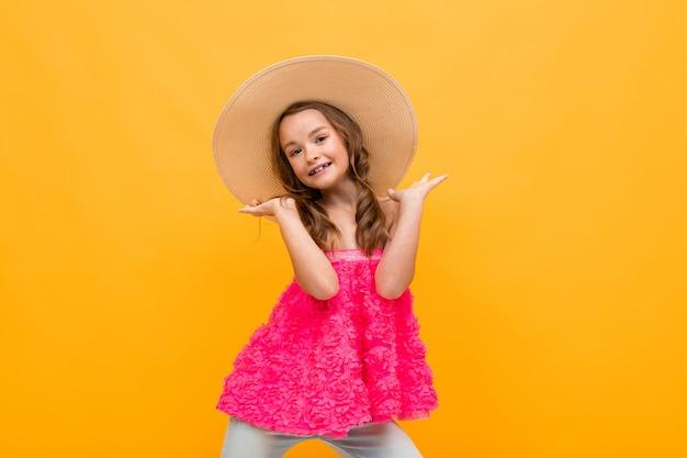 Menina adolescente elegante em uma blusa rosa com um chapéu de palha na cabeça em um estúdio amarelo