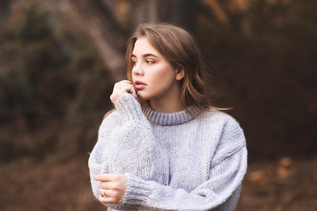 Menina adolescente elegante vestindo uma camisola de malha aconchegante posando ao ar livre. estação do outono. 20s.
