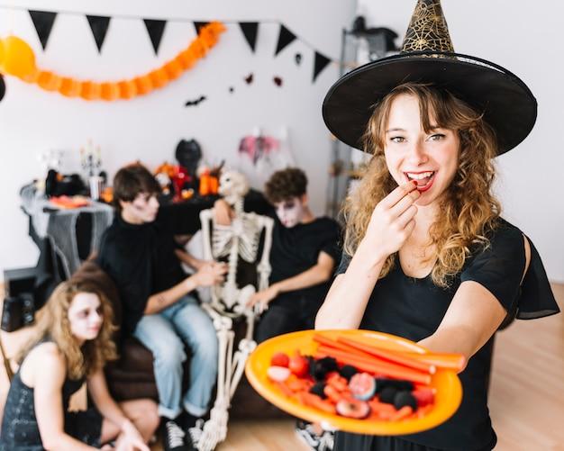 Menina adolescente, em, bruxa, traje, mostrando, prato, com, marmelada, e, sorrindo