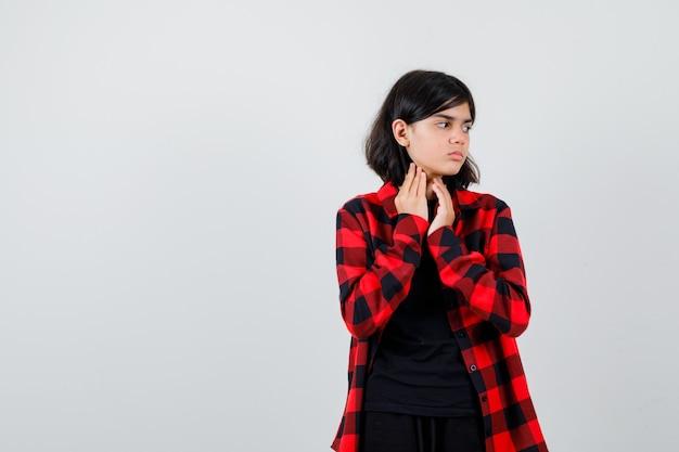 Menina adolescente em camisa casual, de mãos dadas sob o queixo, olhando para o lado e parecendo confusa, vista frontal.