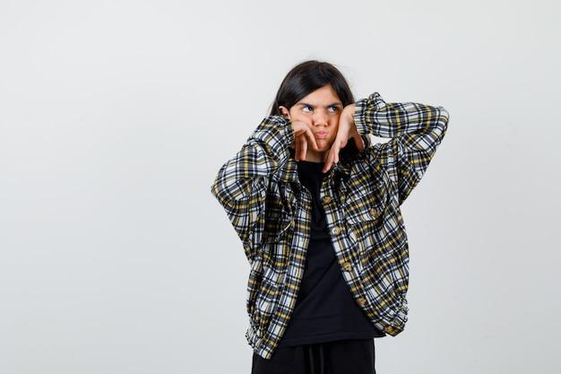 Menina adolescente em camisa casual, mantendo as mãos nas bochechas inchadas, olhando para longe e parecendo mal-humorada, vista frontal.