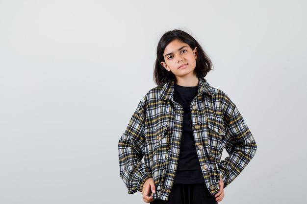 Menina adolescente em camisa casual, posando, mantendo as mãos no quadril e olhando bem-aventurada, vista frontal.
