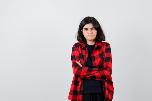 Menina adolescente em camisa casual, segurando os braços cruzados e olhando mal-humorada, vista frontal.
