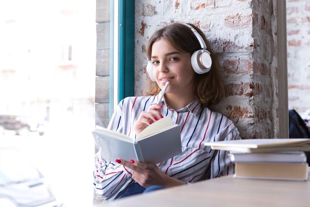 Menina adolescente em fones de ouvido sentado com o livro aberto e olhando para a câmera