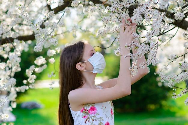 Menina adolescente em máscara médica no jardim primavera. conceito de distância social e prevenção de coronavírus.