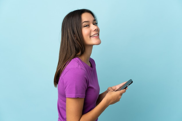 Menina adolescente em rosa enviando uma mensagem ou e-mail com o celular