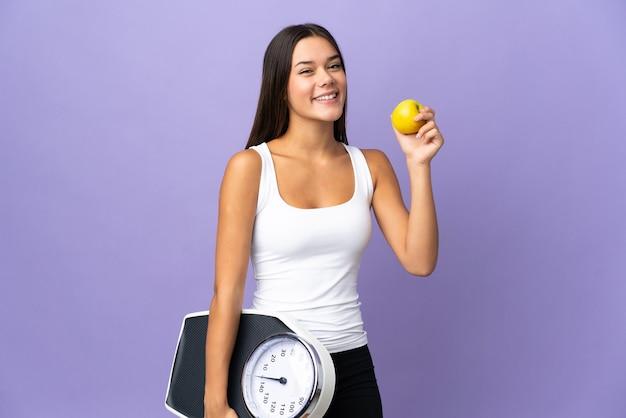 Menina adolescente em roxo com máquina de pesar e com uma maçã