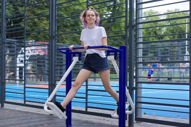 Menina adolescente em simulador de esportes ao ar livre, estilo de vida saudável e ativo de adolescentes, campos esportivos urbanos